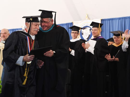 Alvin Lloyd Mann, a 92-year-old graduate of Mount Saint Mary College, receives his degree from acting President James M. Raimo during Saturday's commencement ceremony.