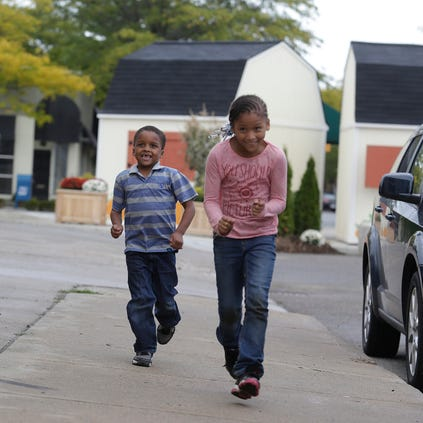 Children run down Kercheval Drive in Detroit with the barns of the Grosse Pointe Park farmers market in the background.