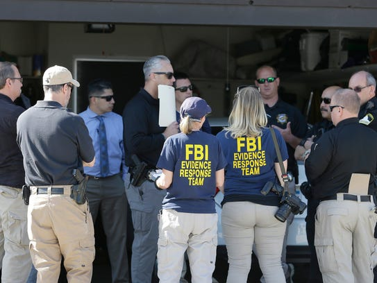 Authorities huddle outside a home searched in connection