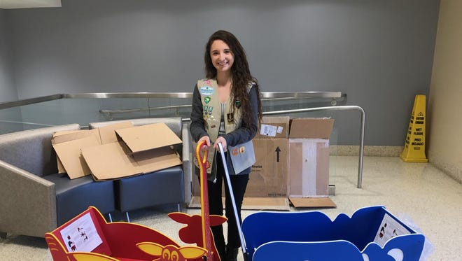 Nicole Shaheen holds two of three IV carts that she raised money to purchase for Providence Children's Hospital.