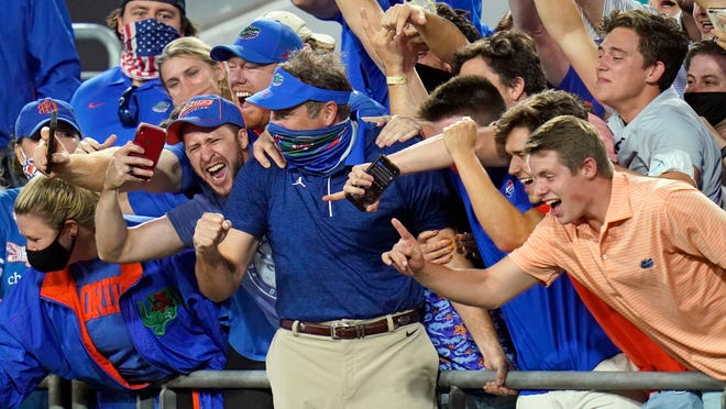 Florida coach Dan Mullen, center, celebrates with fans in the stands Saturday after the Gators defeated Georgia in Jacksonville.