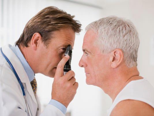 Doctor examining patients eye in doctors office
