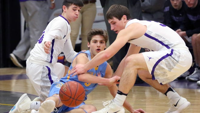 The ball escapes New Berlin Eisenhower's Dominick Quick (left), Joe Lang and New Berlin West's Mason Church at Eisenhower on Feb. 16.