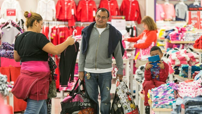 Shoppers Manuel Orellano, center, with his daughter Marcela, left, and her son Manuel, 6, shop for children's clothing at JCPenney at the Glendale Galleria shopping mall in Glendale, Calif. in November.