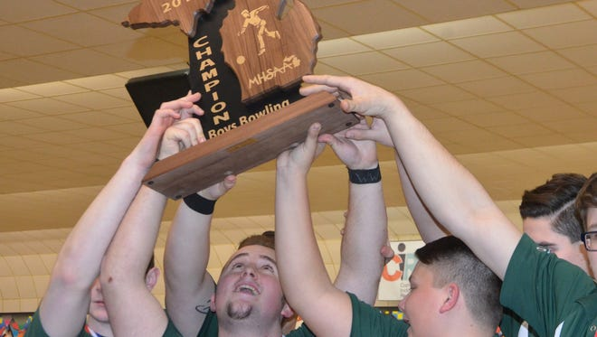 Pennfield senior Max Jackson and his teammates lift up the MHSAA Division 3 Boys Bowling State Championship Trophy on Friday at M-66 Bowl in Battle Creek.