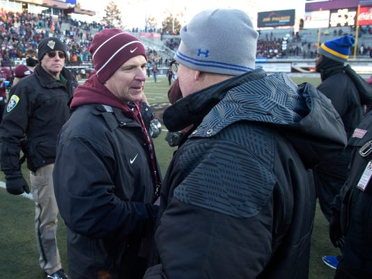FILE- In this Nov. 28, 2015 file photo Montana head coach Bob Stitt, left, shakes hands with South Dakota State head coach John Stiegelmeier, right, after a first round game in the NCAA college Football Championship Subdivision playoff, in Missoula, Mont. Montana athletics director Kent Haslam said Monday, Nov. 20, 2017 he is not renewing the contract of coach Stitt after three seasons. (AP Photo/Patrick Record,File)