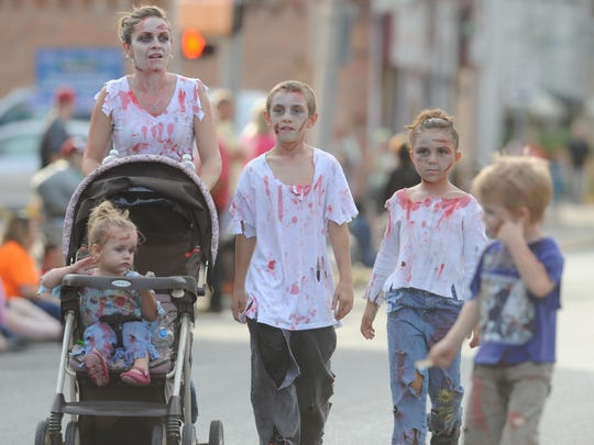 A family of zombies walks on East Main Street during