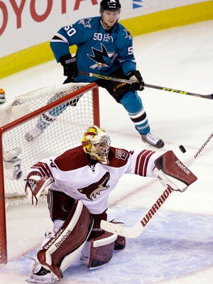 Arizona Coyotes goalie Louis Domingue stops a shot on goal in front of San Jose Sharks' Chris Tierney (50) during the first period of an NHL hockey game on April 3, 2015, in San Jose.