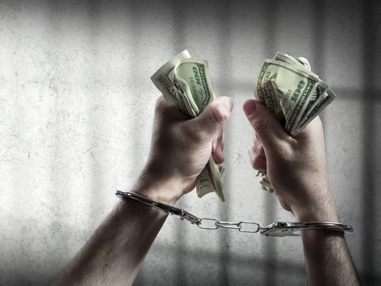 arrest for corruption - handcuffed holding dollars