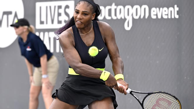 Serena Williams returns a shot to her sister Venus Williams during her three-set win Thursday in a WTA tournament in Nicholasville, Ky.