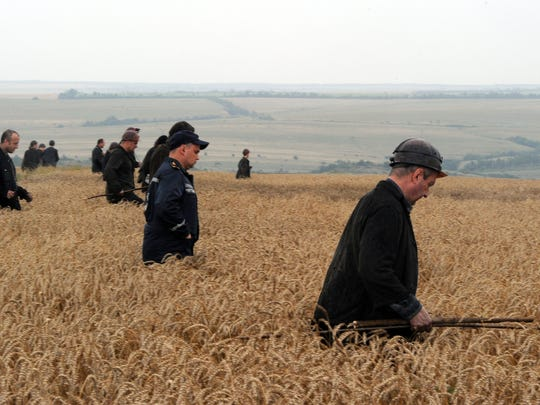 A group of Ukrainian miners assist rescue workers in the search for bodies of victims in a wheat field at the site of the crash of a Malaysian airliner.