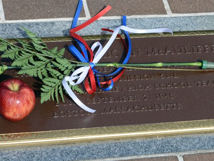 A flower and an apple lie on the plaque of astronaut