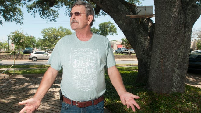 Beekeeper Clarence Prater Jr. talks on Thursday, May 18, 2017, about the process of removing a colony of bees from a tree in a parking lot at 401 E. Chase St. in Pensacola.