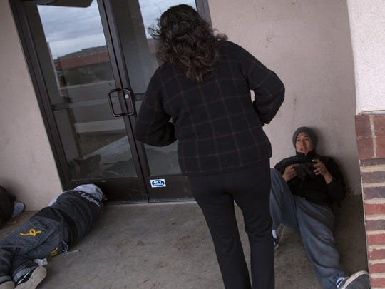 Debbie Magruder, manager and director at the Well Recovery Club, talks on Thursday with Lyle Whitney as he waits for The Roof, a homeless shelter, to open. Magruder handed Whitney a pair of gloves as he waited.