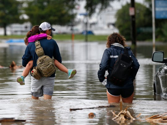Don Noel carries his daughter Alexis, 8, with his wife Lauren, right as they walk through a flooded roadway to check on their boat in the West End section of New Orleans, Wednesday, June 21, 2017.
