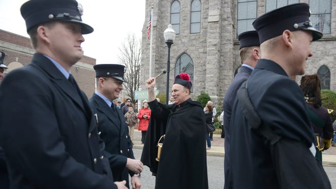 Monsignor William Hodge blesses members of the Gloucester City Fire Department during a celebration of first responders day at St. Mary's Church.