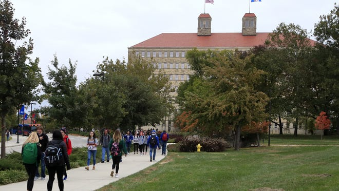 Students walk in front of Fraser Hall on the University of Kansas campus in Lawrence, Kansas.