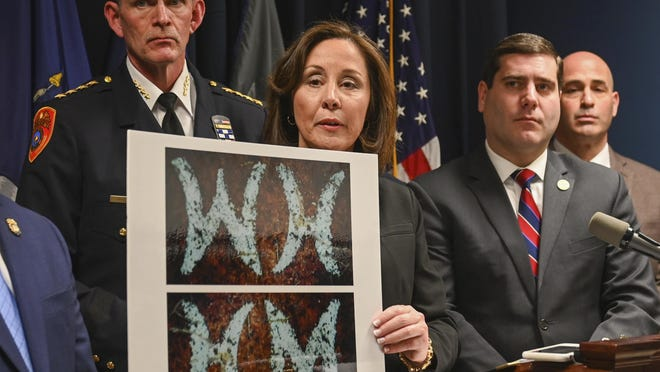 Suffolk County Police Commissioner Geraldine Hart shows a photograph with the initials on a belt, showing either an HM or WH, depending on the angle, during a press conference at police headquarters in Yaphank on Thursday.