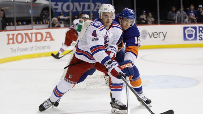 New York Rangers' Adam Clendening (4) and New York Islanders' Ryan Strome (18) reach for the puck during Thursday's game.