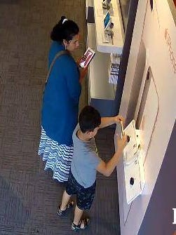 Police say the woman in this surveillance image watched as the boy stole an iPhone from an AT&T store.