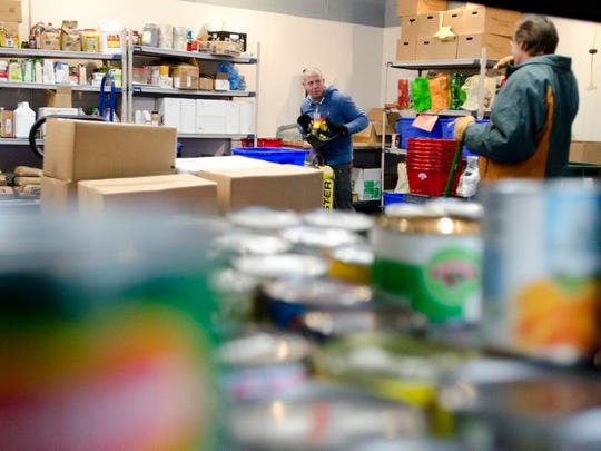 Warehouse coordinator Matt Barron (center) works alongside volunteers at the Chittenden Emergency Food Shelf during the 2013 Giving Season campaign.