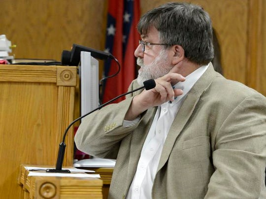 Arkansas Chief Medical Examiner Dr. Charles Kokes demonstrates the area of the neck that was cut on Dr. David Millstein's body during testimony on March 27, 2013, in the Gary Wayne Parks murder trial. Parks was found guilty of the June 2006 murder.