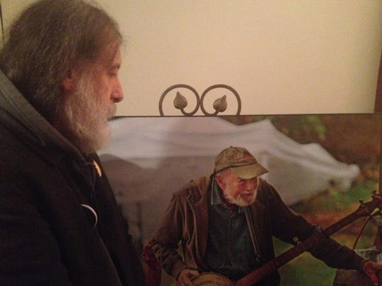 Ken Gale of New York City admires an image of Pete Seeger on display at a memorial held for the late folksinger in Beacon on Sunday.