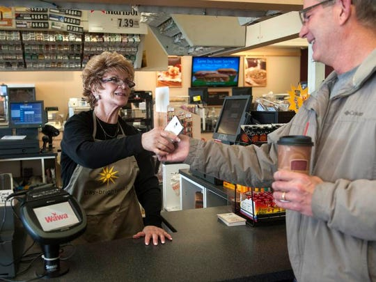 Francine LaTorre, an associate at the Wawa market at the intersection of Greentree and Egg Harbor Roads in Washington Township hands a cell phone back to Bill McMurtrie, of Turnersville, after talking to McMurtrie's son Patrick on the phone in Arizona, at the counter of the store.