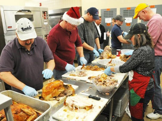 Members of the 120th Fighter Wing and 219th RED HORSE Squadron carve the turkeys for the Danny Berg Memorial Christmas Dinner several years ago.