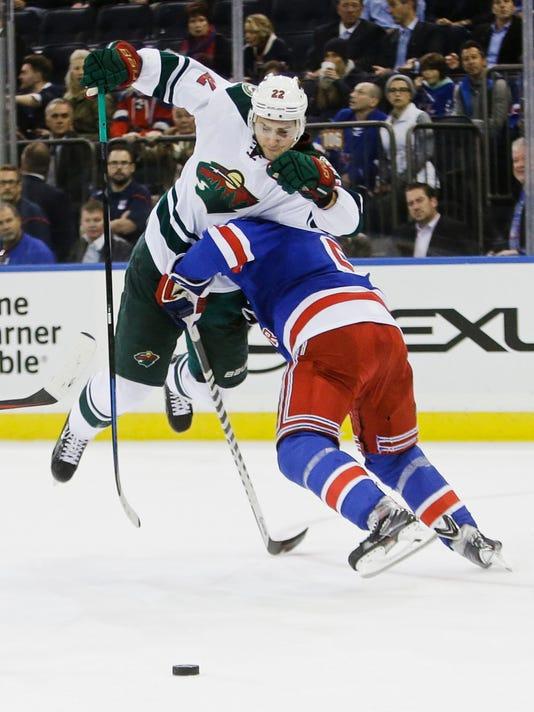 New York Rangers' Dan Girardi (5) checks Minnesota Wild's Nino Niederreiter (22), of Switzerland, during the first period of an NHL hockey game Monday, Oct. 27, 2014, in New York. (AP Photo/Frank Franklin II)