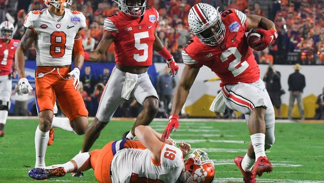 Clemson defensive back Tanner Muse trips up Ohio State running back J.K. Dobbins.