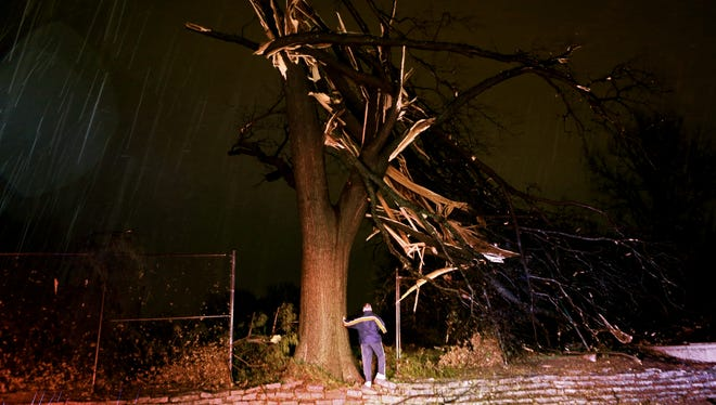 A man surveys damage after a tornado hit and knocked trees down, damaging homes and cutting power early Thursday, April 3, 2014, in University City, Mo.