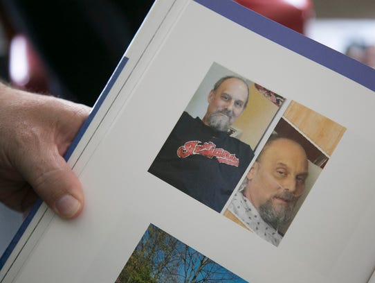 Steve Reeder shows photos of himself in a family scrapbook