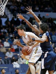 McQuaid's Josh Purcell in the mix near a basket with Jakhi Lucas and a UPrep teammate at Blue Cross Arena at the War Memorial.