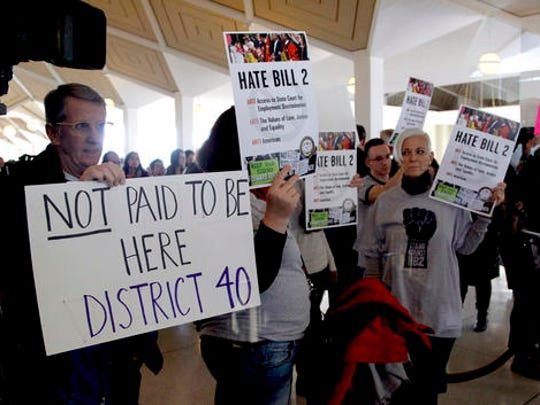 Opponents of HB2 hold signs outside the North Carolina House chambers gallery as the North Carolina General Assembly convenes for a special session at the Legislative Building in Raleigh, N.C. on Wednesday, Dec. 21, 2016. North Carolina's legislature reconvened Wednesday to decide whether enough lawmakers are willing to repeal a 9-month-old law that limited LGBT rights, including which bathrooms transgender people can use in public schools and government buildings.