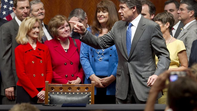 Then-Gov. Rick Perry gathers with lawmakers moments before signing a law that expanded abortion restrictions in 2013. Three years later the law was struck down by the U.S. Supreme Court, in an opinion by Ruth Bader Ginsburg.