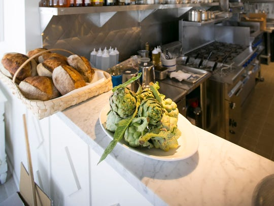 Artichoke and bread in the open kitchen area at Chris