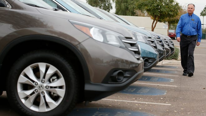 Mike Johnson, a sales manager at a Honda dealership, walks past a row of Honda CRVs in Tempe, Ariz.
