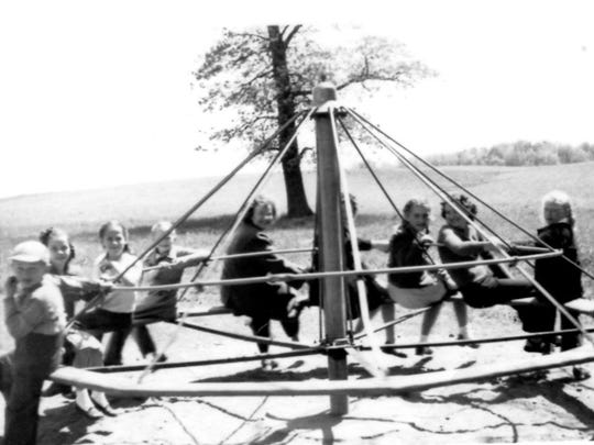 School children play on the District 132 merry-go-round
