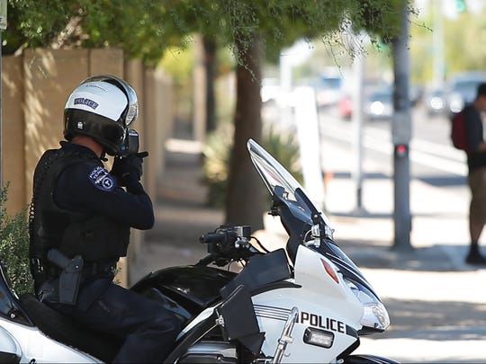 A Tempe police officer checks traffic speed with a