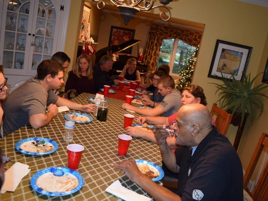 Coy Williams (lower right) has dinner with Wilmington Police Lt. Dan Selekman's family.