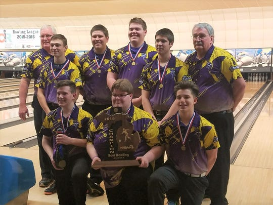 Members of the Bronson boys bowling team pose with their 2018 Division 4 state championship trophy at M-66 Bowl on March 2, 2018.