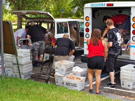 Lehigh Acres letter carriers drop off donated food to during a previous year's national Stamp Out Hunger food drive.