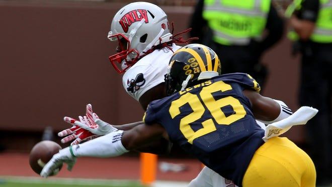 Michigan's Jourdan Lewis knocks the football away from UNLV's  Devonte Boyd in the second quarter at Michigan Stadium in Ann Arbor Saturday, September 19, 2015.