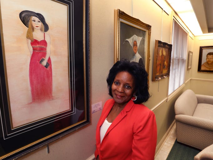 "Fishers resident Dr. Mattie Lee Solomon poses next to her painting, ""White Shoulders"" on Wednesday, July 23, 2014 that is part of an exhibit of African-American art, ""Flava Fresh,"" on display at the Fishers Town Hall, 1 Municipal Dr., through September 5. The annual juried exhibition was curated by D. DelReverda-Jennings of Indianapolis."