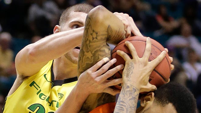 Oregon State's Eric Moreland (15) is fouled by Oregon's Ben Carter as they wrestle for a rebound in the first half of an NCAA college basketball game in the Pac-12 men's tournament.