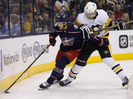 Columbus Blue Jackets' Alexander Wennberg, left, of Sweden, tries to control the puck as Pittsburgh Penguins' Jamie Oleksiak defends during the second period of an NHL hockey game Sunday, Feb. 18, 2018, in Columbus, Ohio. (AP Photo/Jay LaPrete)