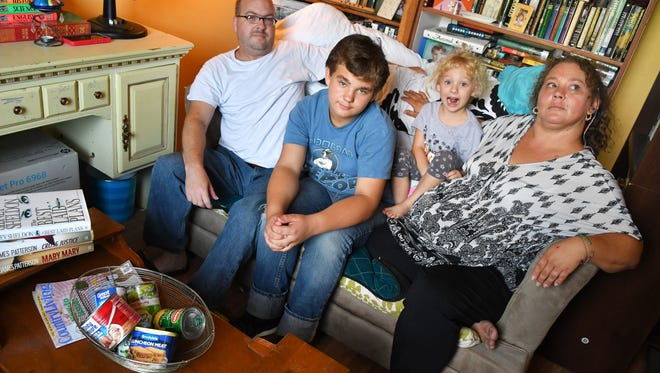 David Light and his wife Summer Burch with children, Jeremiah, 12, and Zoe, 5, on The Couch, the internet famous abandoned furniture that they helped decorate and started a Facebook page for. They plan to steam clean it and wash the cushions and make it available for future charity events, due to it's popularity. In the foreground is some of the books and left over canned goods that were left at the scene.