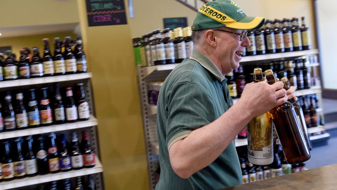 Harlow Flory of Dover Township has two hand fulls as he heads to the counter of the  Bottle Shop during the downtown shop's opening day.