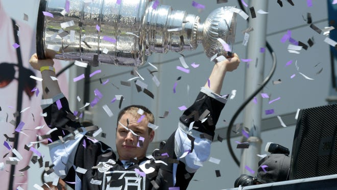 Confetti flies as Los Angeles Kings captain Dustin Brown lifts the Stanley Cup on Monday.